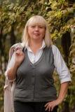走在秋天公园的资深女商人 一个经典衣物样式的一名妇女 服装的端庄的妇女 2 business woman 库存图片