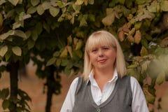 走在秋天公园的资深女商人 一个经典衣物样式的一名妇女 服装的端庄的妇女 2 business woman 免版税库存图片