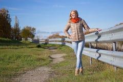走在秋天公园的年轻可爱的妇女 免版税库存图片
