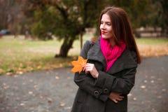 走在秋天城市公园的愉快的妇女 多雨天气和黄色树 免版税图库摄影