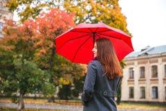 走在秋天城市公园的愉快的妇女 多雨天气和黄色树 库存图片