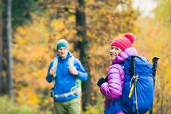 走在秋天森林的男人和妇女愉快的夫妇远足者 库存照片