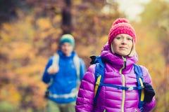 走在秋天森林的男人和妇女愉快的夫妇远足者 免版税库存图片