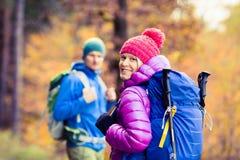 走在秋天森林的男人和妇女愉快的夫妇远足者 图库摄影