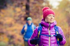 走在秋天森林里的愉快的夫妇远足者 免版税库存照片