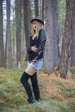 走在秋天森林里的美丽的女孩 免版税图库摄影