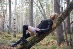 走在秋天森林里的美丽的女孩 免版税库存图片