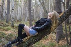 走在秋天森林里的美丽的女孩 免版税库存照片