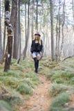 走在秋天森林里的美丽的女孩 图库摄影