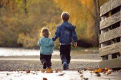 走在秋天湖附近的兄弟和姐妹 库存图片