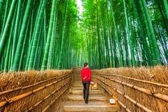 走在竹森林的妇女在京都,日本 免版税库存图片