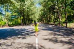 走在线的年轻美丽的亚裔女孩画象在路中部  免版税库存图片
