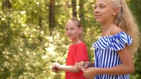 走在绿色公园的两个女孩在好日子 进来在绿色树背景的公园的慢动作女朋友在夏天 股票视频