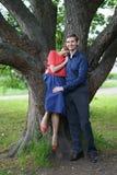 走在绿色夏天公园的俏丽的白种人爱夫妇,有微笑、亲吻和拥抱 库存照片