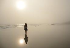 走在美丽的有雾的海滩的女孩 库存图片