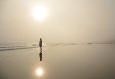 走在美丽的有雾的海滩的女孩 图库摄影