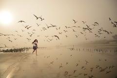 走在美丽的有雾的海滩的微笑的女孩 图库摄影