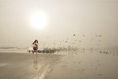 走在美丽的有雾的海滩的微笑的女孩 免版税库存照片