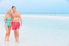 走在美丽的热带海的资深浪漫夫妇 库存图片