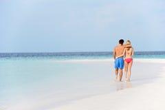 走在美丽的热带海滩的浪漫夫妇 库存照片