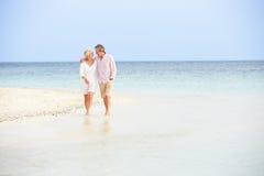 走在美丽的热带海滩的浪漫资深夫妇 库存照片