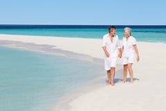 走在美丽的热带海滩的资深浪漫夫妇 图库摄影