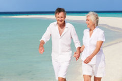 走在美丽的热带海滩的资深浪漫夫妇 免版税库存图片