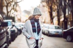 走在美丽的秋天城市街道的愉快的年轻妇女戴五颜六色的围巾和温暖的帽子 图库摄影
