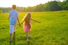 走在美好的日落的孩子 库存照片