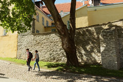 走在老市街道上的青年人塔林,爱沙尼亚 免版税库存照片