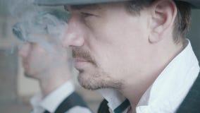 走在老被毁坏的大厦的两位抽烟的匪徒接近的画象  影视素材