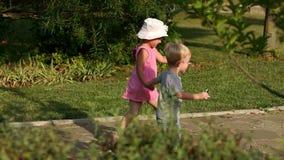 走在胡同的两个逗人喜爱的孩子在夏天停放 股票视频