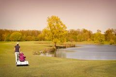 走在航路的女性高尔夫球运动员 免版税库存照片