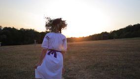 走在草甸佩带的花小环和种族成套装备的女孩在日落本质上 影视素材