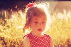 走在草甸的哀伤的逗人喜爱的女孩在夏天日落 免版税库存图片