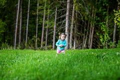 走在草的小婴孩 童年和l的概念 库存图片