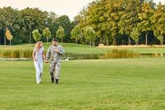 走在草的愉快的可爱的夫妇 免版税库存照片
