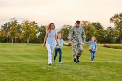 走在草的愉快的家庭 免版税图库摄影