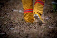走在草的消防队员衣服 库存图片
