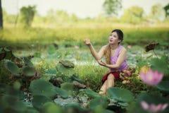 走在莲花领域的亚裔美丽的妇女 免版税库存照片
