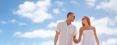 走在蓝天的愉快的微笑的夫妇 库存照片