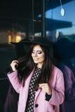 走在街道上的一个年轻美丽的时髦的女人的室外画象 式样佩带的时髦的桃红色外套,黑 免版税库存照片