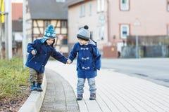 走在街道上的两个小兄弟姐妹男孩在德国村庄 免版税库存照片