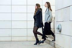 走在街道上的两个年轻人女实业家在办公室buildi附近 免版税图库摄影