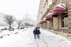 走在街道上的人们在一多雪的天 免版税库存图片