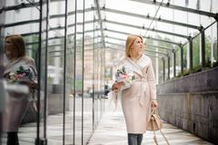 走在街道上的女孩拿着美丽的玫瑰色颜色花束 库存图片