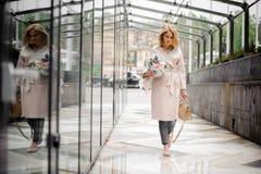 走在街道上的女孩拿着美丽的花束 免版税库存照片