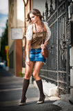 走在街道上的女孩短裙和袋子。城市布局的年轻欧洲女孩 免版税图库摄影