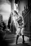走在街道上的女孩短裙和袋子。城市布局的年轻欧洲女孩 免版税库存图片