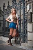 走在街道上的女孩短裙和袋子。城市布局的年轻欧洲女孩 库存照片